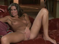 Adrienne Manning is with slender figure removes her blue panties to play with her snatch. Cute brunette with small tits and long legs has a good tine masturbating on the sofa with her high heels on.